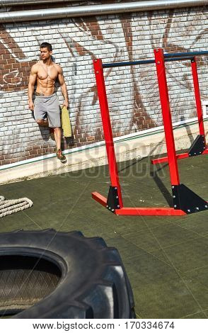 Half-naked sporty man leaning against wall at outdoor gym.