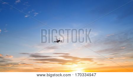 Silhouette of drone quadrocopter against the sunset sky
