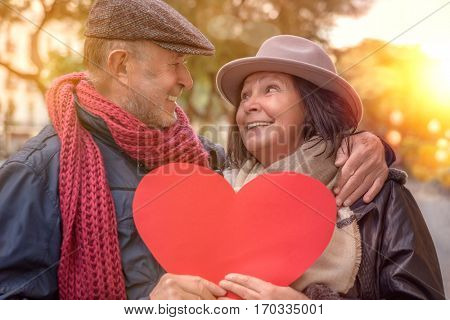 heart holding senior couple in the city