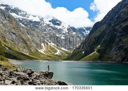 A Woman Hiker On a Lake Shore in The Southern Alps Lake Marian Fjordland National Park New Zealand