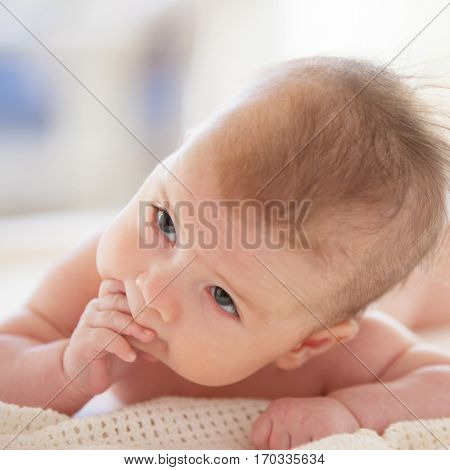 Close up portrait of cute baby. Adorable baby in white sunny bedroom. Family morning at home. Child relaxing on white bed. Textile and bedding for kids. Kid looking into the camera