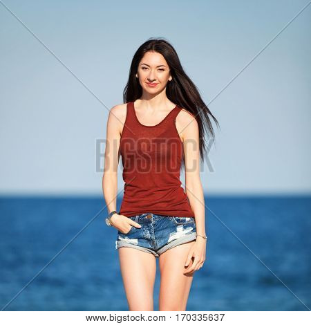 Young beautiful fashion woman standing on the beach. Happy outdoor summer lifestyle. Vacation. Ocean beach relax. Sexy stylish woman with long hair in jean shorts and red tanktop walking at the beach