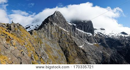 A Woman Hiker on a Ridge Top in Fjordland National Park.  Milford Sound, Southern Alps, New Zealand.