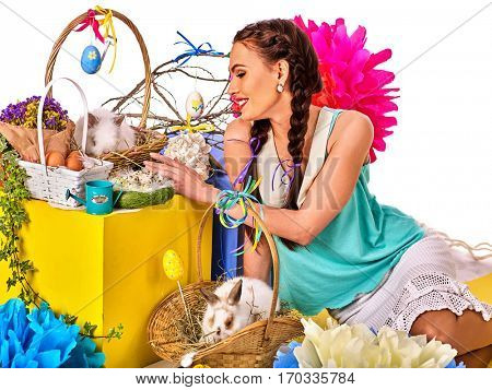 Easter girl holding bunny and eggs. Holiday style holding and group of rabbits in basket with flowers. Isolated. Woman with present box. White background.