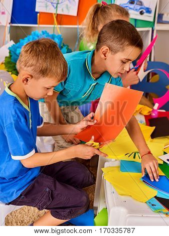 Child cutting paper in class. Kids development and social lerning children in school. Children's project in kindergarten. Pictures into background. Girl and boy together.