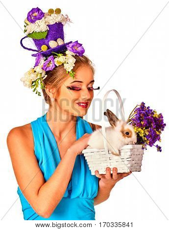 Easter girl holding bunny and eggs. Woman with holiday hairstyle and make up holding rabbit in basket with flowers. White background.