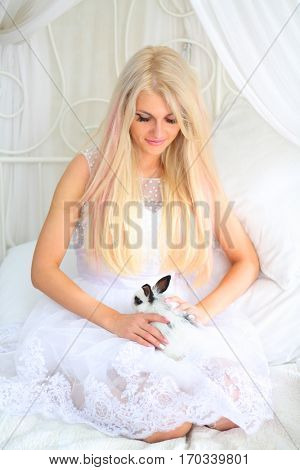 Blonde in bride white dress holds funny fluffy cub of rabbit on bed