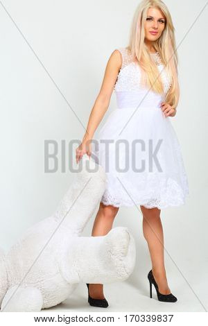 Beautiful woman in white dress drags big toy bear in white studio