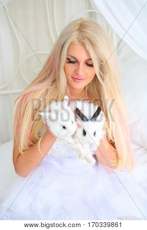 Blonde in bride white dress holds funny fluffy cubs of rabbit on bed