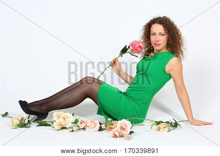 Pretty curly oman in green dress holds rose and sits on floor among roses in white studio