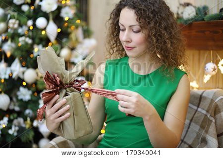 Woman in green dress opens christmas present near adorned fir tree
