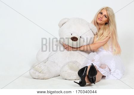 Woman in white dress sits and embraces big toy bear in white studio