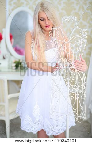 Woman in white dress touches white hanger in cozy light room
