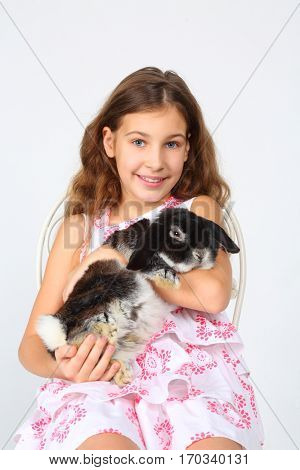 Happy smiling girl in dress holds funny rabbit and sits on chair in white studio