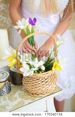 Woman in white dress takes flower from basket on table in studio, noface