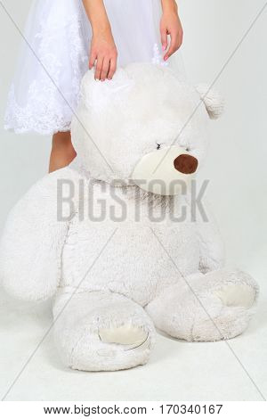 Woman in white dress stands with big toy bear in white studio, noface