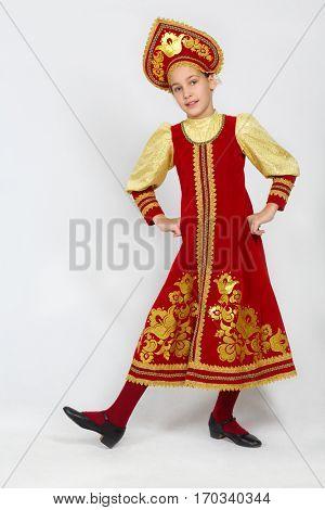 Pretty girl in red russian folk costume dances in white studio