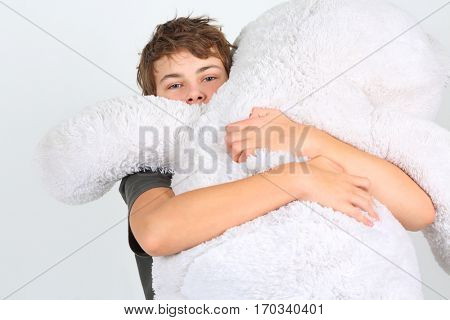 Boy teenager in grey embraces large white toy bear in studio