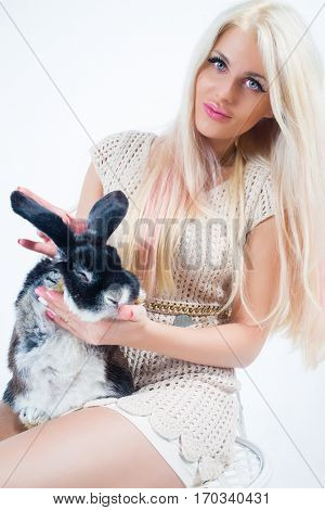 Blonde with long hairs sits on chair with funny rabbit in white studio