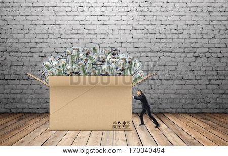 Businessman is pulling a huge box of money in front of him on the background of brick wall and wooden floor. Making money. Profit and income. Business development