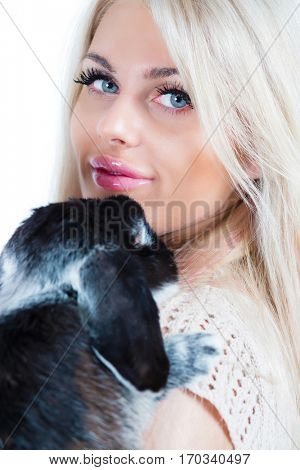 Cute young blonde hugs funny black rabbit isolated on white, close up
