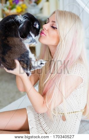 Pretty young blonde kisses fluffy black rabbit in cozy bedroom
