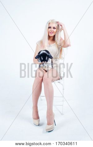 Blonde with long hairs sits on chair with black rabbit in white studio
