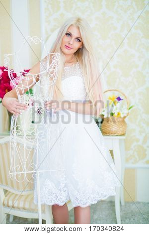 Pretty woman in white dress touches white hanger in cozy light room