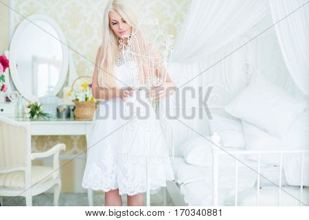 Young woman in white dress touches white hanger in cozy bedroom