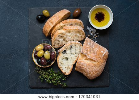 Italian food ingredients background with Sliced bread Ciabatta, olive oil, olives and thyme on dark stone slate. Top view