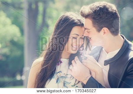 Passion and love. Couple. Harmony, tenderness, peace and love between two lovers. Young men and young women embracing outdoors. Intense feeling and fiery passion. Bright light behind.