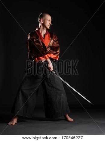 Man wearing kimono holding japanese sword, practicing  on dark studio background