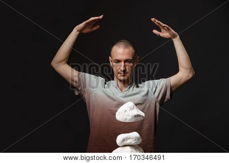 Telekinesis concept  - man making stones levitating with power of thought, dark studio background