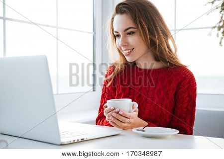 Happy beautiful young woman using laptop and drinking coffee in cafe