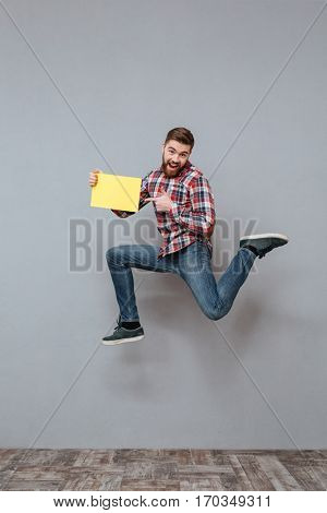 Image of attractive bearded man holding copyspace blank jumping over grey background and pointing.