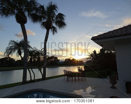 Lakeside View Of Palm Trees And Orange Fiery Sunset