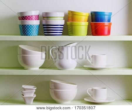 Variety of ceramics on shelf. Colorful bowls, cups and white dishware.