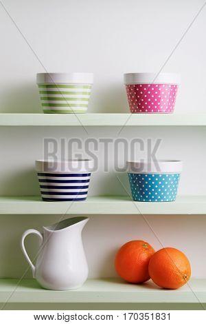 Colorful bowls on a kitchen shelf. A kitchen shelf unit holding striped and spotted bowls. Kitchen shelf arrangement.