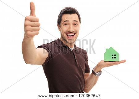 Delighted man making a thumb up gesture and holding a model house isolated on white background