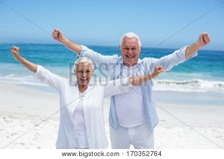 Senior couple outstretching their arms at the beach