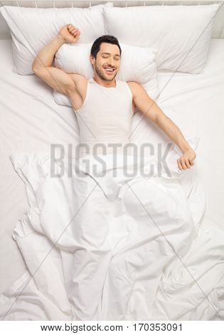 Young man lying in bed and stretching himself