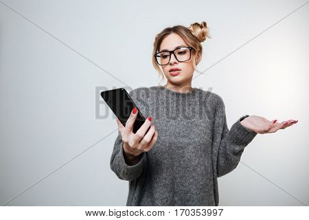 Displeased woman in sweater and eyeglasses with phone in hand. Isolated gray background