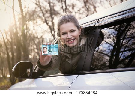 Woman with driving license in car