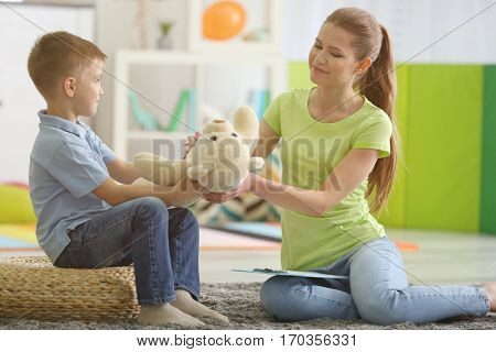 Young female psychologist working with little boy in office