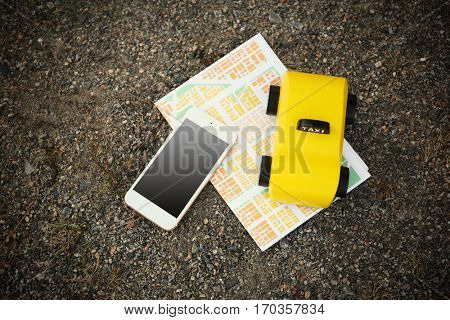 Yellow toy taxi with map and phone on ground