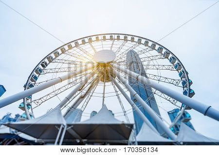 Big ferris wheel with cityscape against cloudy sky .