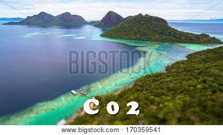 C 0 2 quote concept with Tropical paradise island with bright smooth mirror sand & crystal clear water with rocky shore in the island of Semporna, Borneo, ideal for print card and poster design.