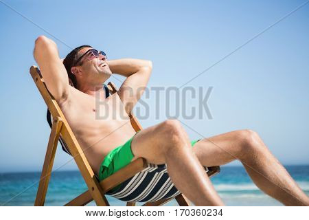 Man sitting and relaxing on deck chair on the beach