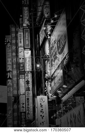 TOKYO - JUNE 19, 2016:  Billboards, ads and lights in Shinjuku's Kabuki-cho district in Tokyo, Japan. The area is a nightlife district known as Sleepless Town. Black and white.