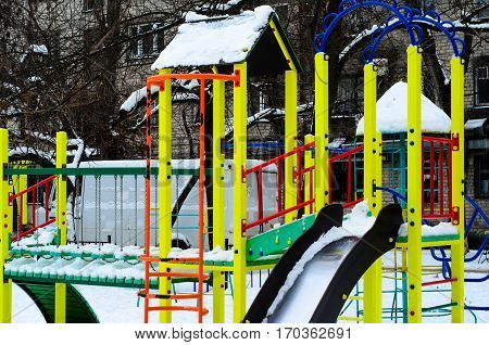 Children playground covered with snow on winter